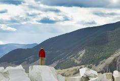 O indivíduo na moda em um revestimento vermelho está em uma rocha de mármore e na vista para o vale do verão Aventura do esporte  fotos de stock royalty free