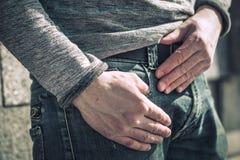 O indivíduo nas calças de brim está guardando sua mão em seu bolso fotografia de stock