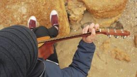 O indivíduo no chapéu feito malha senta-se em uma pedra e joga-se a guitarra jogando a opinião da guitarra de cima de filme