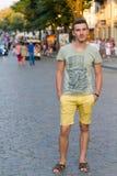 O indivíduo no short amarelo no fundo da cidade Fotos de Stock Royalty Free