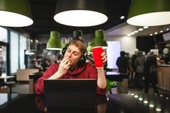 O indivíduo nos fones de ouvido senta-se no café na tabela, come-se um hamburguer e trabalha-se em um portátil foto de stock royalty free