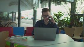 O indivíduo nos vidros que fala no telefone ao sentar-se em um portátil filme