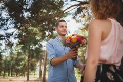 O indivíduo novo é traz flores a sua amiga na menina da floresta A com uma bicicleta toma flores de um indivíduo nas madeiras fotos de stock royalty free