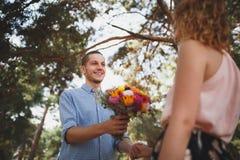 O indivíduo novo é traz flores a sua amiga na menina da floresta A com uma bicicleta toma flores de um indivíduo nas madeiras fotos de stock