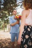 O indivíduo novo é traz flores a sua amiga na menina da floresta A com uma bicicleta toma flores de um indivíduo nas madeiras imagens de stock