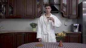 O indivíduo novo considerável em um roupão branco está bebendo o café ao estar na cozinha na manhã A tabela filme
