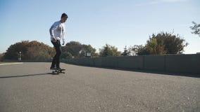 O indivíduo novo do moderno em calças de brim escuras, em uma camiseta leve e em um chapéu escuro está montando um skate fora O s vídeos de arquivo