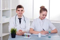 O indivíduo novo e a menina de dois doutores, sentando-se na mesa e sorrindo, a menina escrevem algo fotografia de stock royalty free