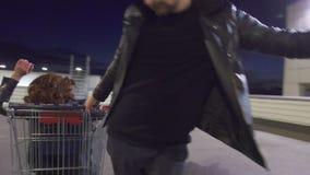 O indivíduo novo empurra um outro indivíduo vestido como a mulher que senta-se no carrinho de compras filme