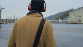 O indivíduo novo escuta música com fones de ouvido que anda na cidade vídeos de arquivo