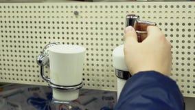 O indivíduo novo está considerando acessórios do banheiro em uma loja dos materiais de construção filme