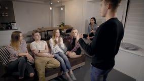 O indivíduo novo está mostrando a pantomima para seus amigos que sentam-se em um sofá na sala, jogando o jogo das charadas junto filme