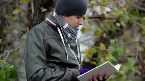 O indivíduo novo lê livro interessante no parque, bestseller, educação filme