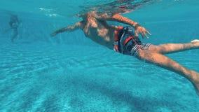 O indivíduo novo nada debaixo d'água em uma piscina vídeos de arquivo