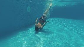 O indivíduo novo nada debaixo d'água em uma piscina filme