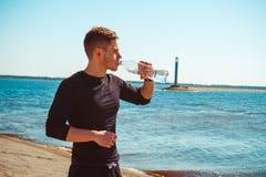 O indivíduo novo que descansa após o exercício, bebidas molha imagem de stock royalty free