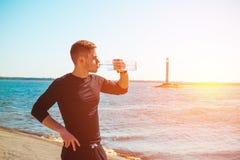 O indivíduo novo que descansa após o exercício, bebidas molha imagens de stock royalty free
