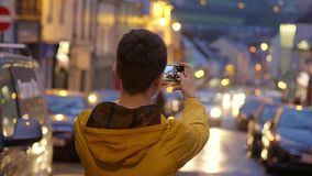O indivíduo novo toma fotos com o telefone celular vídeos de arquivo
