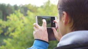 O indivíduo novo toma fotos da paisagem do outono no telefone vídeos de arquivo