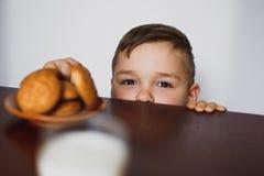 O indivíduo olha para fora de debaixo da tabela e quer pegarar as cookies Imagens de Stock Royalty Free