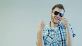 O indivíduo positivo alegre nos óculos de sol é de dança e de júbilo, emoção humana video estoque