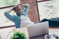 O indivíduo preto alegre está olhando em sua tela do portátil, em seu lugar de trabalho, com os braços atrás da cabeça, descansar foto de stock royalty free