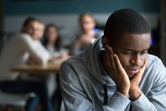 O indivíduo preto senta-se apenas no sofrimento do café da discriminação racial imagem de stock