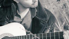 O indivíduo que joga a guitarra no b&w da natureza video estoque