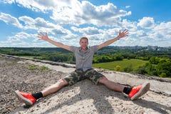 O indivíduo que senta-se no telhado com braços e pés abertos Imagem de Stock