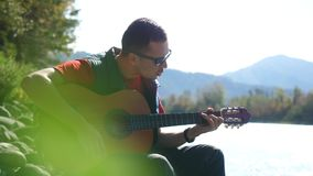 O indivíduo que veste óculos de sol joga em uma música do canto da guitarra que senta-se pelo rio da montanha no dia ensolarado 3 video estoque