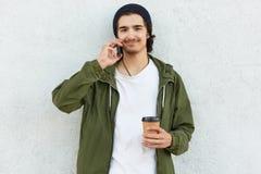 O indivíduo satisfeito do moderno tem a conversação telefônica com amigo, guarda o telefone celular moderno, leva a xícara de caf fotos de stock royalty free