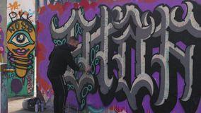 O indivíduo tira grafittis na parede com lata de pulverizador video estoque