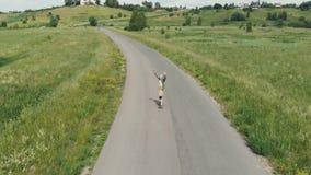 O indivíduo vai na estrada em um longboard, em olhares na câmera e em chamadas com ele Siga-me O indivíduo monta um longboard sob vídeos de arquivo