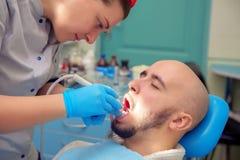 O indivíduo considerável trata os dentes da cárie no escritório dental Fotos de Stock Royalty Free