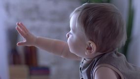 O infante bonito está gastando o lazer na sala em fundo unfocused filme