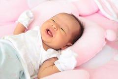 O infante recém-nascido da face encontrou-se na cama cor-de-rosa Imagem de Stock