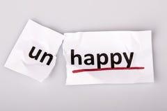 O infeliz da palavra mudado a feliz no papel rasgado imagem de stock