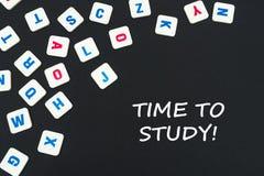 O inglês coloriu letras quadradas dispersadas no fundo preto com tempo do texto estudar imagens de stock