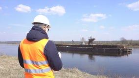 O inspetor na veste do sinal monitora a qualidade do trabalho da extração da areia do rio para a construção, indústria video estoque