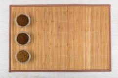 O instante liofilizou, café granula e à terra na esteira de bambu Imagens de Stock Royalty Free