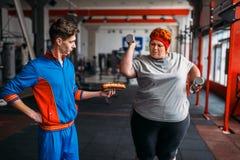 O instrutor com hotdog força a mulher gorda a exercitar fotografia de stock