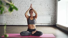 O instrutor consideravelmente fêmea da ioga está demonstrando torções do corpo na posição de lótus, está esticando e está fazendo video estoque