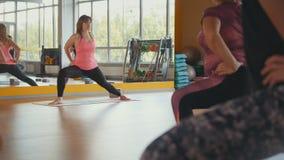 O instrutor da aptidão treina as mulheres excessos de peso em um gym Imagem de Stock