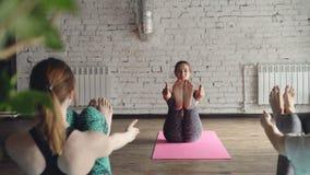 O instrutor da ioga está demonstrando variações diferentes da pose do barco, falando aos estudantes e ao riso Relaxamento amigáve filme