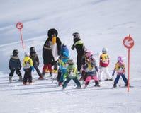 O instrutor do esqui no terno de pinguim estuda crianças Estância de esqui em A Imagens de Stock Royalty Free