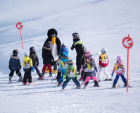 O instrutor do esqui no terno de pinguim estuda crianças Estância de esqui nos cumes, Áustria, Zams o 22 de fevereiro de 2015 Imagens de Stock