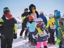 O instrutor do esqui no terno de pinguim estuda esquiadores novos Estância de esqui Fotografia de Stock Royalty Free