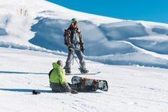 O instrutor do Snowboarder ensina o homem que senta-se com snowboard Imagem de Stock