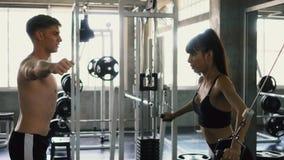 O instrutor dos esportes que guia seu cliente fêmea que faz o cabo cruza-se sobre o exercício da caixa no gym video estoque