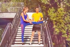 O instrutor ensina a menina fazer o esticão de exercícios Fotos de Stock Royalty Free